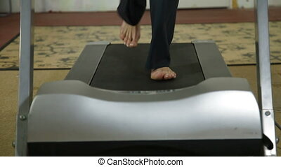 Feet on treadmill - female legs running on treadmill at home