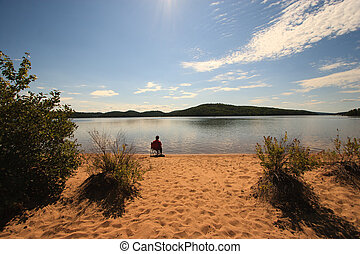Alone on the Beach of a Calm Wilderness Lake
