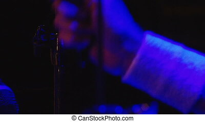 Drummer's hand in dark blue light