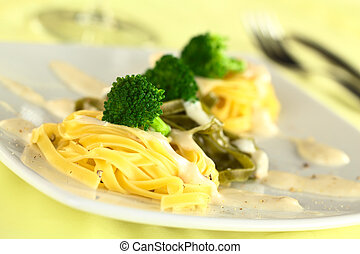 Broccoli on fettuccine - Broccoli florets on yellow and...