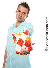 Gift young man - A young man wearing a blue shirt offering a...