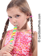 Girl sucking on a candy stick