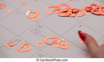 Small hearts on the calendar - Woman removes a small hearts...