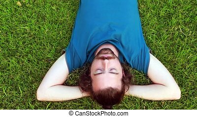 Young guy lie down on grass