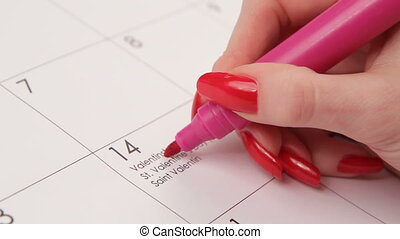 Red heart in calendar - Woman draws the red heart in...