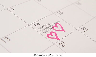 Two hearts in calendar - Woman fills in red color two hearts...