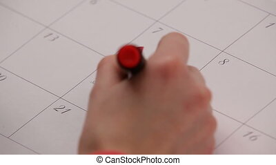 Red heart in calendar. HD - Woman draws the red heart with...