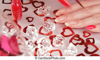 Nail polish - Woman makes manicure near a diamonds and red...