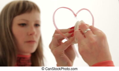 Girl wipes off small hearts from the mirror the with...