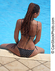 A woman sits on the edge of the swimming pool