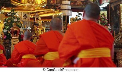 buddhist monks pray in temple