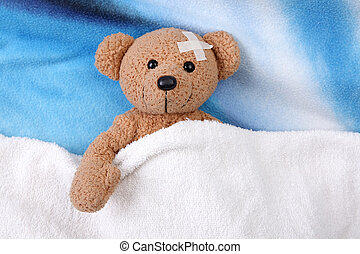 teddy bear sick with adhesive bandage over bed. close up
