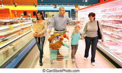 Family in supermarket - Happy family walking along the...