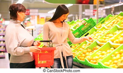 Buying fruit - Mother and daughter buying fruit