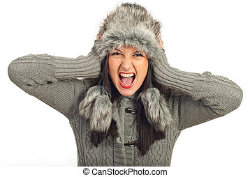 Crazy winter woman holding head in fur hat and screaming...