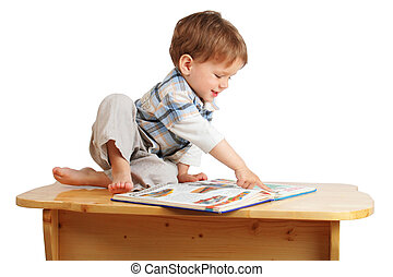 One smiling playing children reading the book on the desk