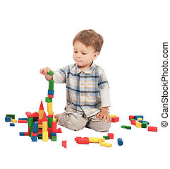 Little boy building the tower with bricks