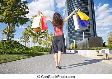 happy shopper and skyscrapers - brunette woman with shopping...