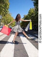 happy shopper on crosswalk - brunette woman with shopping...