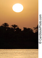 Egyptian Landscape - The sun sets over the Nile river in...