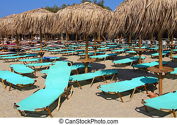The beach near the blue sea with sun beds and umbrellas