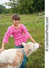 Village life. Girl with a calf