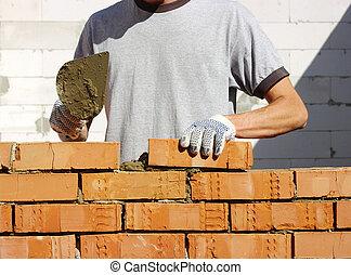 bricklayer laying bricks to make a wall