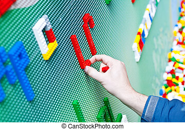 Child playing with plastic toy bricks - A Child playing with...