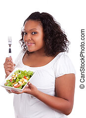 Young african american woman eating salad, isolated on white...
