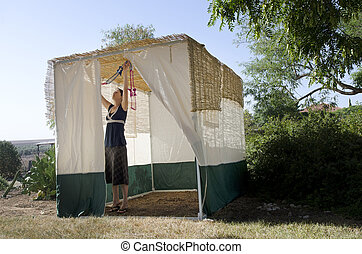 Jewish Festival of Sukkot - A Jewish woman is decorating...