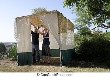 Jewish Festival of Sukkot - A Jewish couple are decorating...