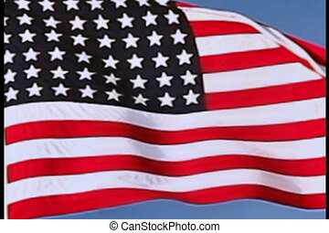 USA flag flying on the wind on blue sky background, closeup...