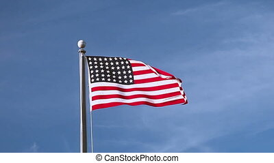 USA flag flying on the wind on blue sky background