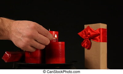 Candles and Gift - A male hand lights the candles. They move...