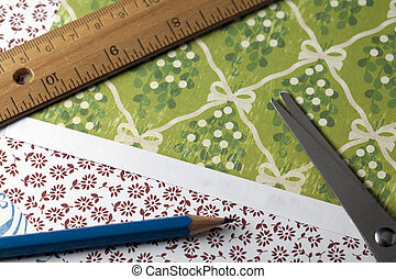 Sissors, pencil and ruler on peices of decorative paper.