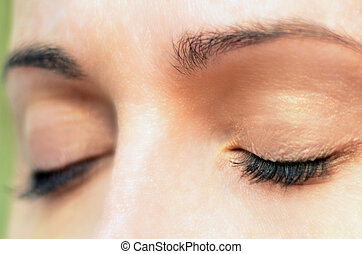 Womans Eyes - Woman relaxes by closing her eyes