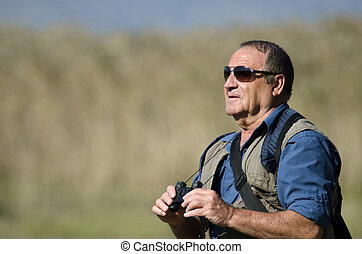 Bird Watcher - A senior hiker and bird watcher is searching...