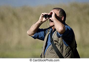 Bird Watcher - A senior hiker and bird watcher is searching...