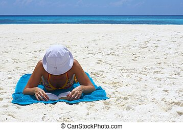 Young women is reading the book on the beach
