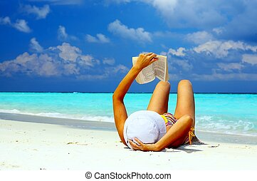 Young women is reading on the coral beach, Maldives