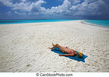 Young women is sunburning on the sandy beach