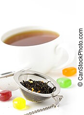 tea strainer with a fragrant black tea and cup in the...