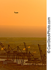 Plane and Cranes at the Port of Barcelona at Sunset