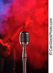 rock live concert - old microphone in the foreground with a...