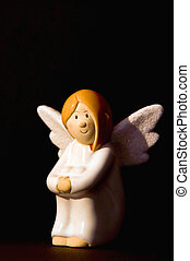 Ceramic angel in the dark - Ceramic angel figure sitting in...
