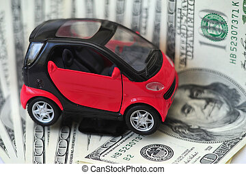 Black and red car over a lot of dollar bills isolated on white (selective focus).