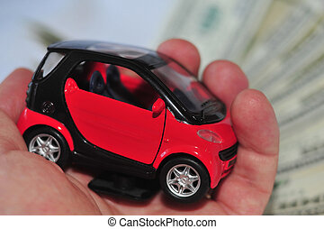 A hand holding a black and red car over a lot of dollar...