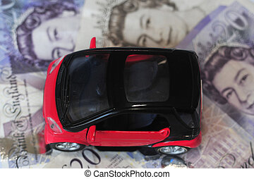 Black and red car over a lot of British Pound Sterling bills isolated on white (selective focus).