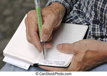 Man writing with pen in notebook - Closeup of man's hand...