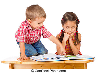 Two smiling children reading book on the desk - Two smiling...